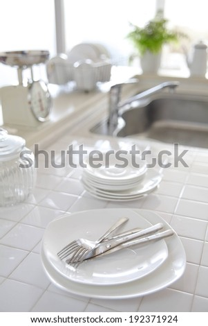 Dishes and cutlery rest on a white tiled kitchen counter in front of a sink. - stock photo