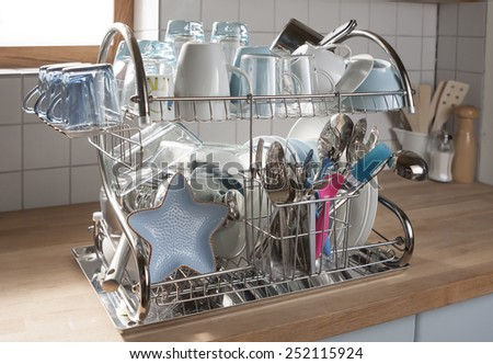 Dishes drying on a metal dish rack in a kitchen - stock photo