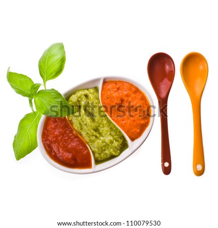 dishes for sauces with three different kinds of sauces, a branch of basil and ceramic spoon isolated on white background - stock photo