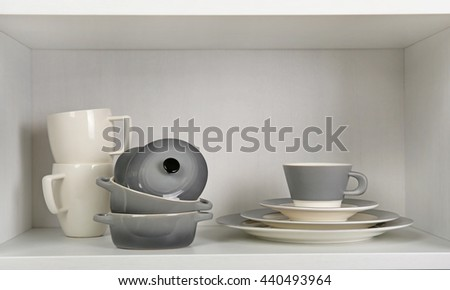 Dishes in cupboard in the kitchen - stock photo