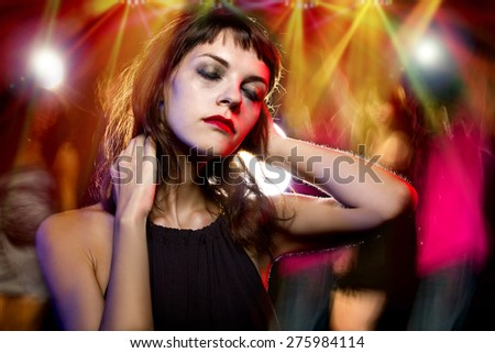 Disheveled drunk or female high on drugs at a nightclub.  Motion blurred party people in the background dancing.  - stock photo