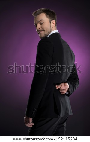 Dishonest businessman. Rear view of smiling businessman holding his fingers crossed and looking over shoulder while isolated on colored background - stock photo