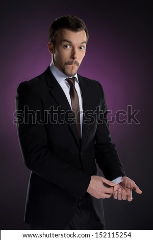Dishonest businessman. Young businessman holding a card in his sleeve while isolated on colored background - stock photo