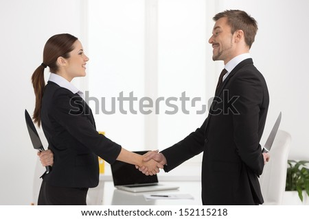 Dishonest partnership. Two young business people shaking hands and holding knifes behind their backs. - stock photo