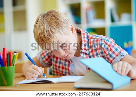 Dishonest schoolboy looking the answer in book at lesson