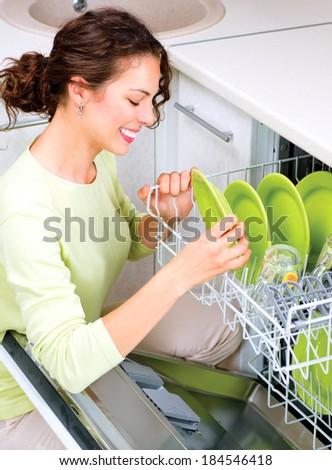 Dishwasher. Happy Young woman in the Kitchen doing Housework. Dishwasher Machine, dishwashing. Wash-up. Smiling Girl using dishwasher machine - stock photo