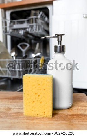 Dishwasher sponge with soap in dispenser tube on background of opened dishwasher machine after cleaning process. Technology timesaving concept. - stock photo