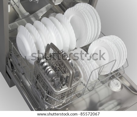 Dishwasher with white plates and steel cutlery - stock photo