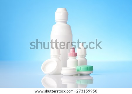 Disinfecting solution for contact lenses and eye drops on blue background - stock photo