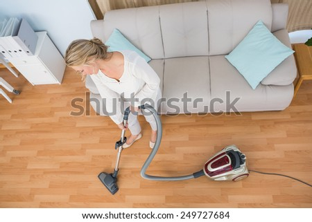 Disinterest woman cleaning her living room at home in the living room - stock photo