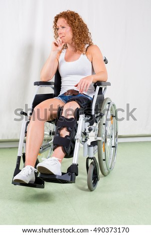 Disinterested woman in wheelchair with hand to lip and brace on her leg sits near white canvas