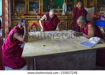Diskit, India - August 20, 2015: Buddhist monks working on a mandala in monastery prayer hall. A mandala is a spiritual and ritual symbol in Indian religions, representing the universe.