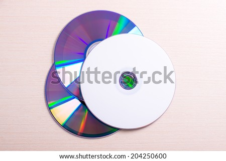 disks on wooden table - stock photo