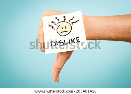 Dislike concept with hand on blue background - stock photo