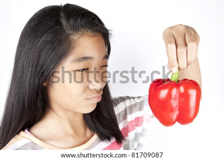 dislike veggie, Asian girl action dislike red bell pepper. - stock photo