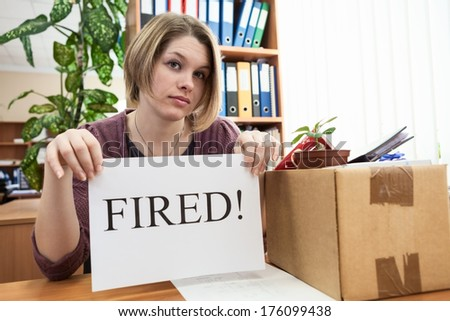 Dismissed worker with sheet of paper with fired word in the office - stock photo