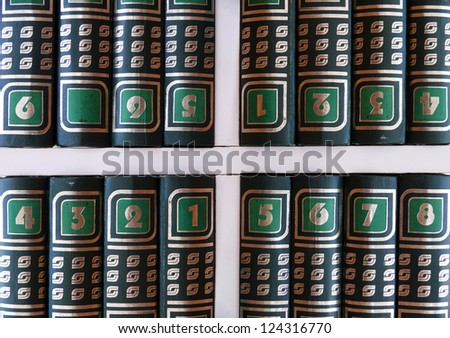 disordered volumes of an encyclopedia on the shelf - stock photo