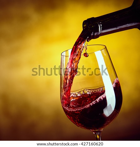 Dispensing red wine from a bottle into an elegant wineglass in a close up view on the liquid being poured over a blurred brown background, square format - stock photo