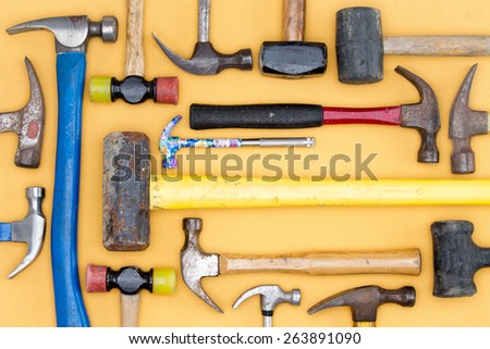 Display of a diversity of hammers in a tool kit for DIY, carpentry, construction, mallets and a sledgehammer in a neat arrangement on a wooden table, overhead view - stock photo