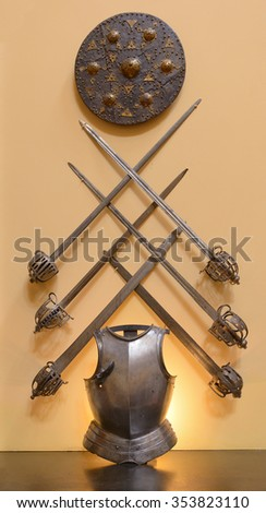 Display of ancient armor consisting of 6 swords, a breastplate and a shield - stock photo
