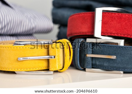 Display of bright colored man belts in a shop or showroom: yellow, red and blue - stock photo