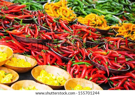 display of colorful peppers at a farmers market stall - stock photo