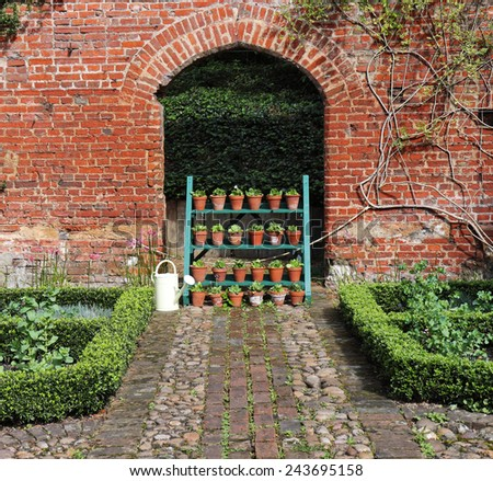 Display of Flowerpots under a red brick archway - stock photo