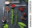 Display of fresh herbs and spices with assorted peppercorns in spoons, star anise and cayenne pepper, fresh parsley, rosemary oregano and bay leaves, overhead view - stock photo