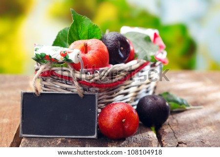 Display of fresh purple and red plums at an outdoor farmers market with a small blank blackboard for your description and price - stock photo