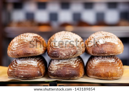 Display of handmade bread loaves on the counter top of a modern bakery to entice customers to buy - stock photo