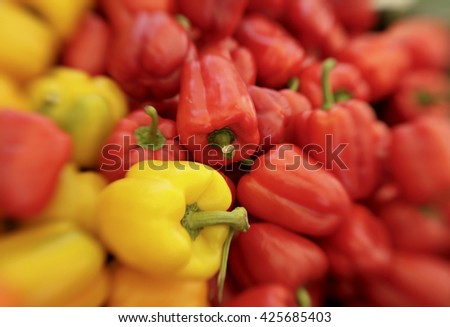 Display of red and yellow bell peppers at a farmer's market in California. (The special effect blur is created with a lensbaby soft focus lens.)