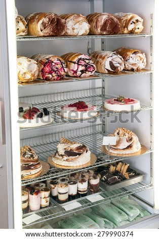 Display of traditional Italian semifreddo cakes and desserts in a refrigerator made from semi frozen ice cream and cream whipped into a mousse parfait and flavored with assorted fruits and flavors