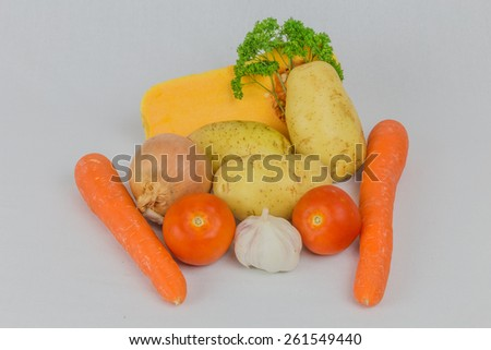 Display of  various fresh vegetables isolated on white background consisting of carrots,garlic,onions,potatoes,pumpkin,tomatoes,cheese and green fresh parsley  - stock photo