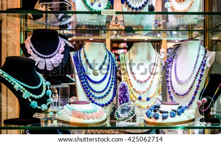 Display with different designs of handmade jewelry on stand. Close-up of handmade jewelry shop window display. Variety of Earrings, Necklace, rings, beads - stock photo