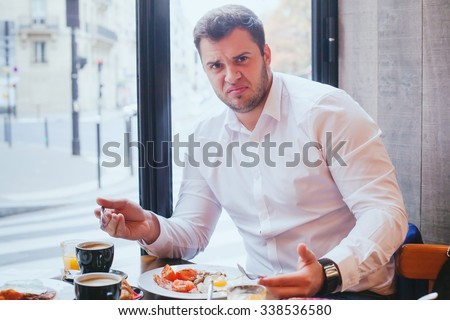 displeased angry customer in restaurant, man unhappy with food and bad service - stock photo