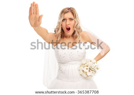 Displeased bride making a stop hand gesture and looking at the camera isolated on white background