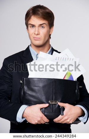 Displeased business man holding big briefcase with documents, isolated on white background. Concept for hard work