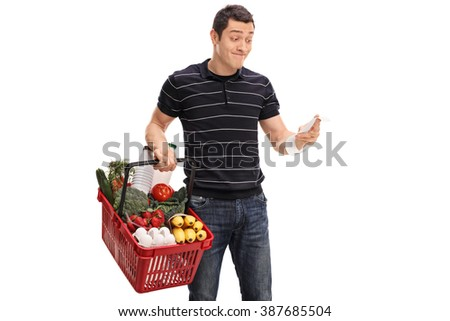 Displeased guy holding a shopping basket full of groceries and looking at the bill isolated on white background