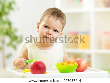 displeased kid with healthy food at kitchen - stock photo
