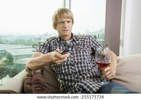 Displeased mid-adult man with wine glass watching television on sofa at home - stock photo