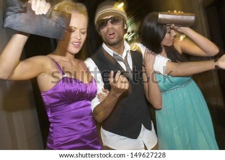 Displeased multiethnic celebrities leaving venue - stock photo