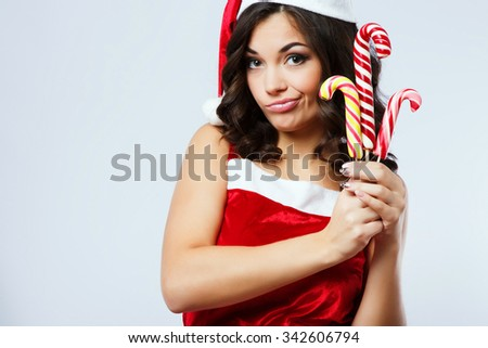 Displeased nice woman, with curly hair, wearing in red santa costume, posing with colorful candies in her hands, on the white background, in studio, close up