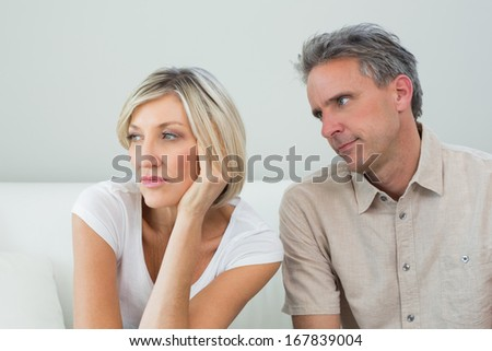 Displeased relaxed couple sitting on sofa after a fight in a house