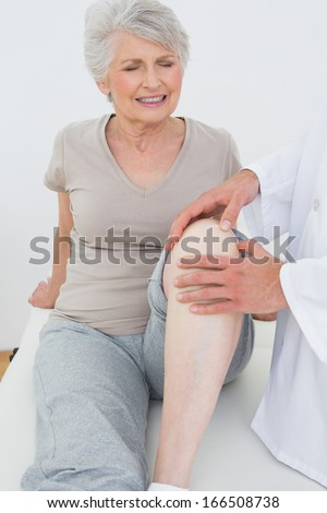 Displeased senior woman getting her knee examined at the medical office - stock photo