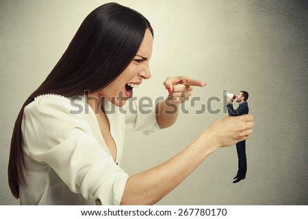 displeased woman holding small man in hand and they shouting at each other. photo on dark background - stock photo