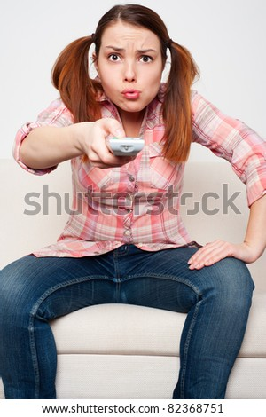 displeased woman sitting on sofa and watching tv - stock photo