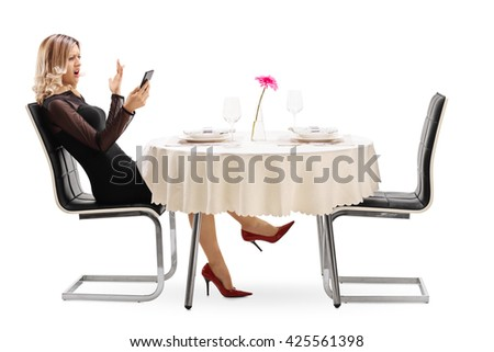Displeased woman waiting for her date seated at a restaurant table isolated on white background - stock photo