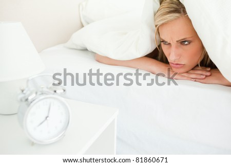 Displeased woman waking up in her bedroom
