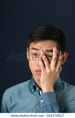 Displeased young Asian man looking at camera through his fingers