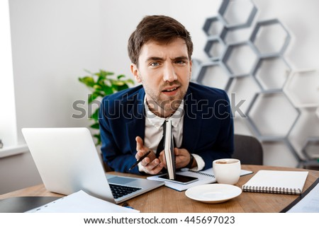 Displeased young businessman sitting at workplace, office background.